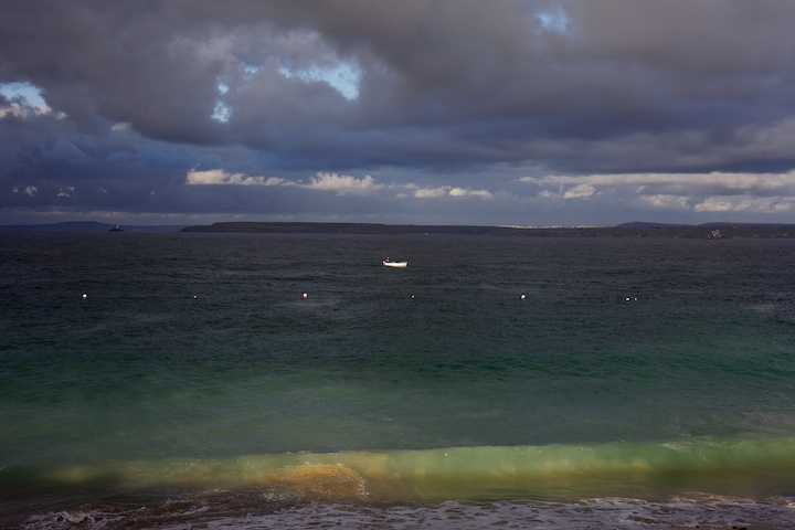 A fishing boat finishes up before the impending storm